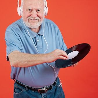 Älterer mann des smiley, der musikaufzeichnung hält
