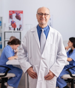 Älterer mann des therapeuten, der vor der kamera steht und das operationssymptom analysiert
