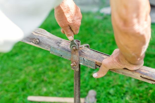 Älterer mann dreht die mutter mit einem schraubenschlüssel