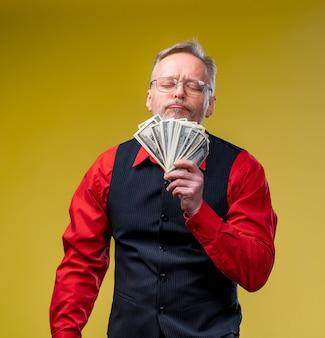 Älterer mann gewann die lotterie, geldfan in der nähe des gesichts des alten mannes. glückstag. menschliche emotionen und mimik