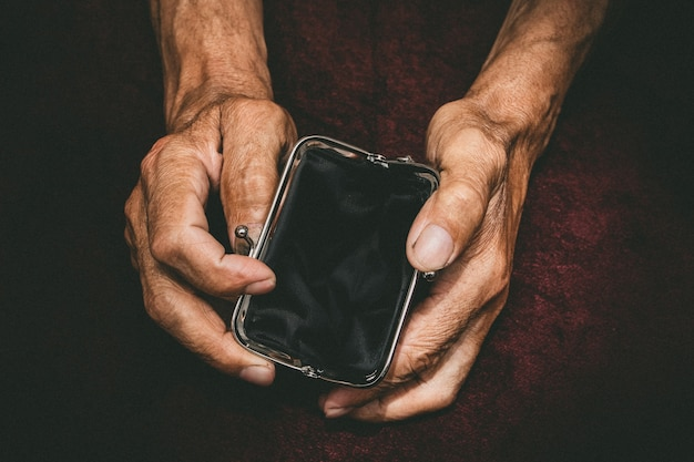 Älterer mann hält in seinen händen eine leere brieftasche.