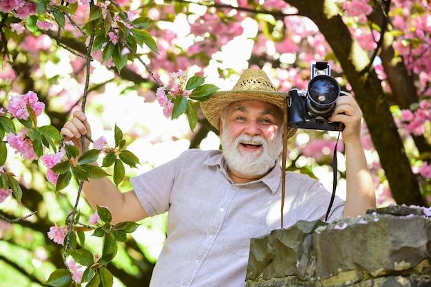 Älterer mann hält professionelle kamera. ruhestand reisen. freizeit genießen. reisen und tourismus. schönheit einfangen. glücklicher großvater. frühlingsferien. reisefoto. fotograf im blühenden garten.