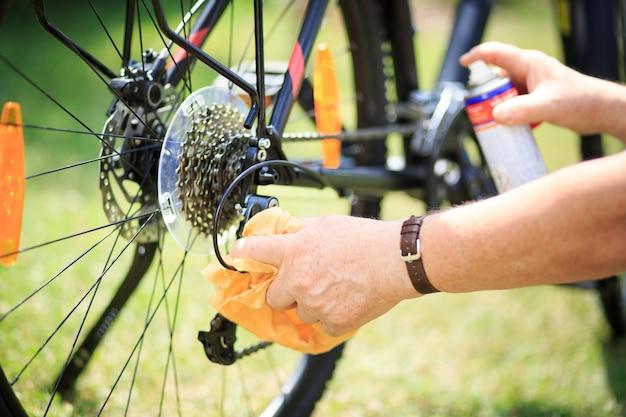 Älterer mann hände, die das fahrrad durch sprühen und lappen reinigen