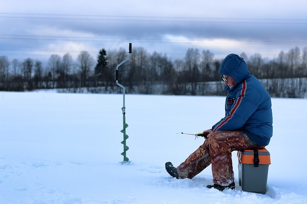 Älterer mann hat im winter auf dem see gefischt