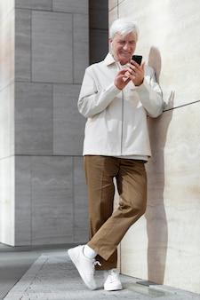 Älterer mann im freien in der stadt mit smartphone mit ohrhörern