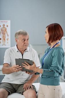 Älterer mann im gespräch mit physiotherapeut