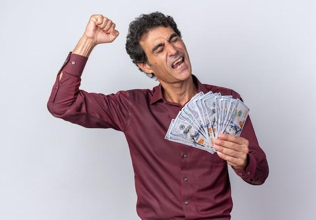 Älterer mann im lila hemd, das bargeld glücklich und aufgeregt die geballte faust hält, die über weißem hintergrund steht