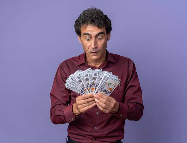 Älterer mann im lila hemd, das bargeld hält, das erstaunt und überrascht auf das geld schaut, das auf blauem hintergrund steht?