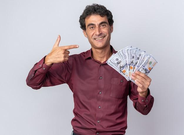 Älterer mann im lila hemd, das bargeld hält und mit dem zeigefinger auf geld zeigt