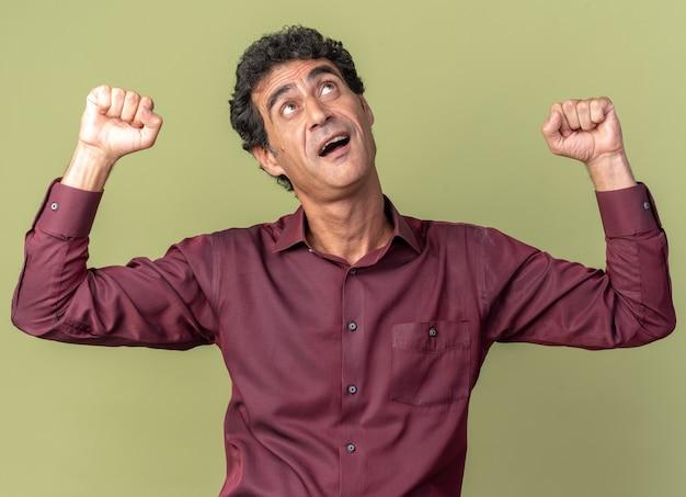 Älterer mann im lila hemd, das glücklich und aufgeregt die fäuste hebt, die über grünem hintergrund stehen