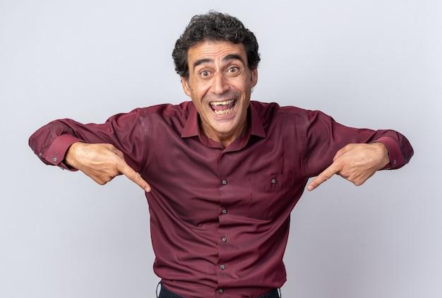 Älterer mann im lila hemd, der glücklich und aufgeregt in die kamera schaut und mit den zeigefingern nach unten zeigt