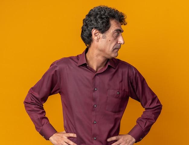 Älterer mann im lila hemd, der mit ernstem gesicht beiseite schaut, das über orangefarbenem hintergrund steht