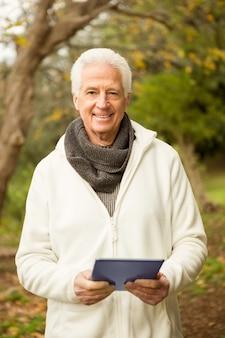 Älterer mann im park unter verwendung der tablette