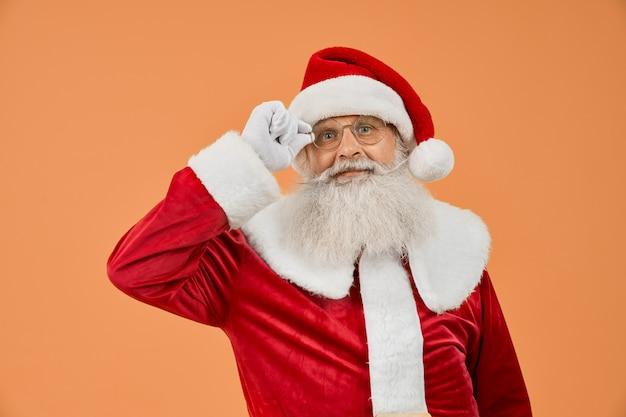 Älterer mann im roten weihnachtsmann-kostüm, das seine brillen trägt