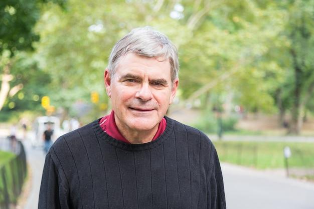 Älterer mann im ruhestand am park, gehend und entspannen sich und lächeln ausdruck