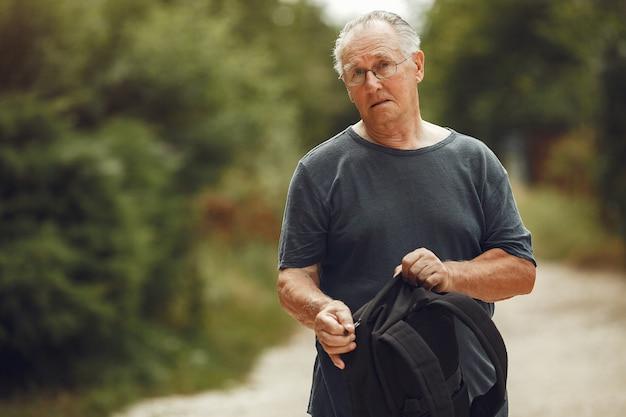 Älterer mann im sommerpark. grangfather mit einem rucksack.