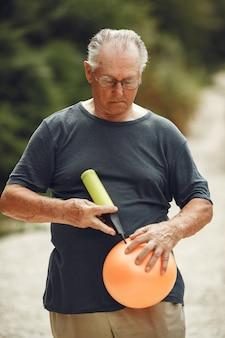 Älterer mann im sommerpark. grangfather mit einer pballpumpe.