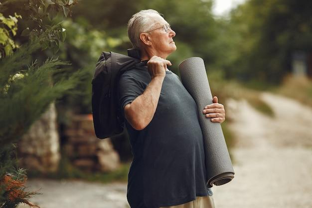 Älterer mann im sommerpark. großvater mit einer matte.