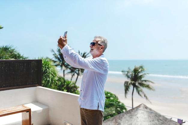 Älterer mann im urlaub, der ein selfie nimmt