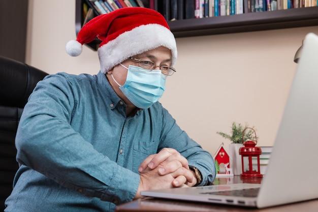 Älterer mann im weihnachtsmannhut spricht unter verwendung des laptops für videoanruffreunde und -kinder. das zimmer ist festlich eingerichtet. weihnachten während des coronavirus.