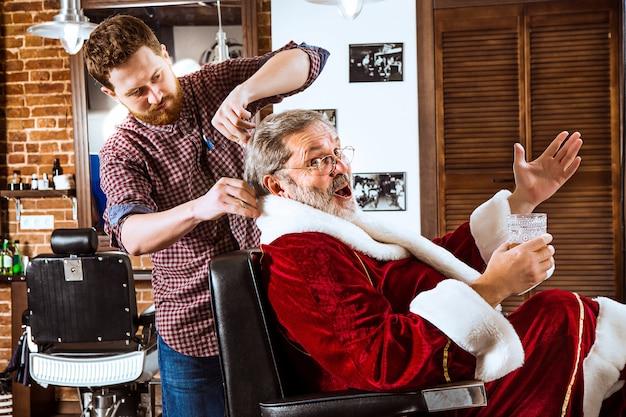 Älterer mann im weihnachtsmannkostüm, das seinen persönlichen meister im friseurladen vor weihnachten rasiert