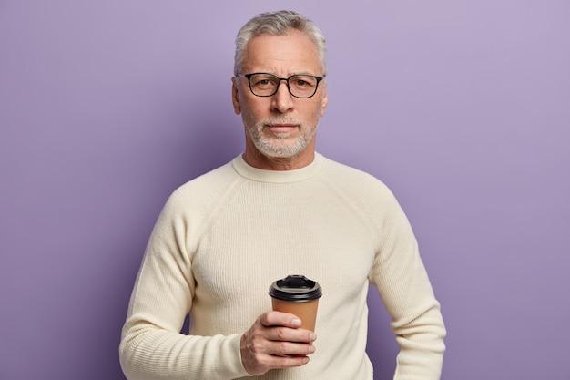Älterer mann im weißen pullover und in den brillen, die kaffeetasse halten