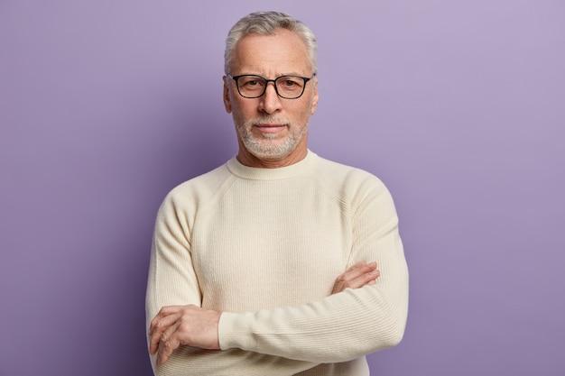 Älterer mann im weißen pullover und in den brillen
