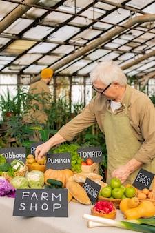 Älterer mann in brille und schürze, die an der theke stehen und bio-lebensmittel für verkauf am bauernmarkt vorbereiten