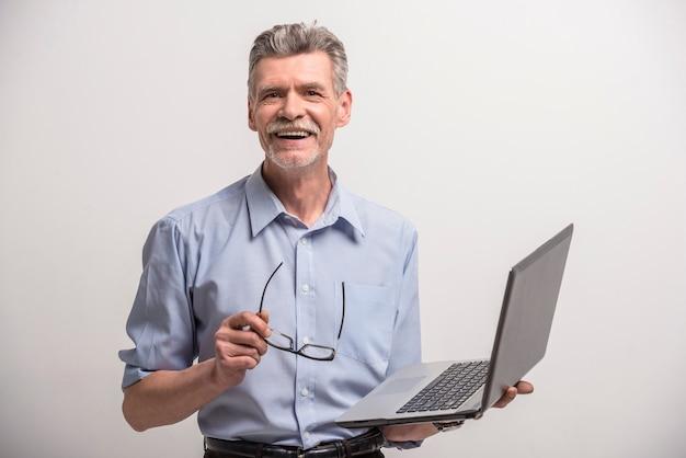 Älterer mann in den gläsern mit laptop
