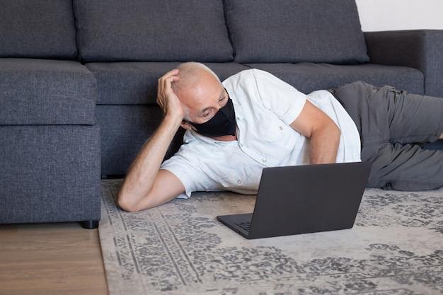 Älterer mann in der medizinischen maske, die am computer zu hause arbeitet
