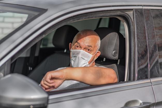 Älterer mann in der medizinischen maske, die ein auto fährt und die kamera betrachtet.