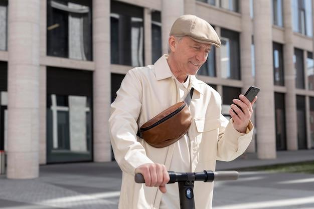 Älterer mann in der stadt mit einem elektroroller mit smartphone