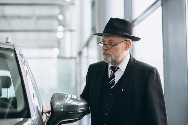 Älterer mann in einem autosalon, der ein auto wählt