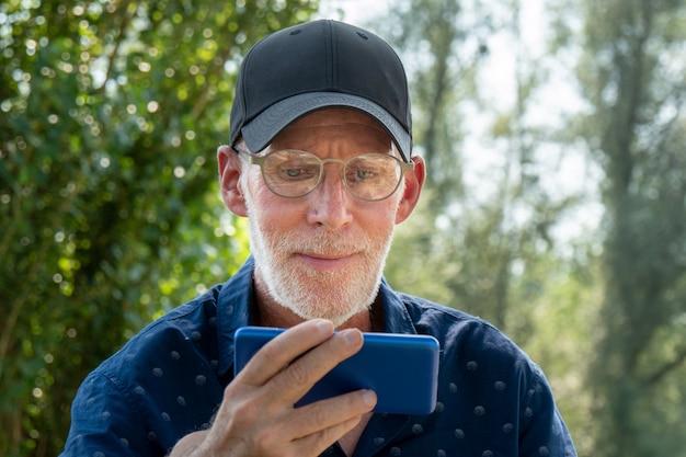 Älterer mann in einem baseballmützenporträt unter verwendung des smartphone