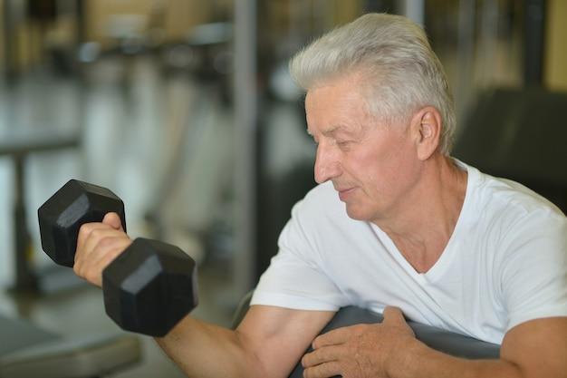 Älterer mann in einem fitnessstudio. training mit hantel