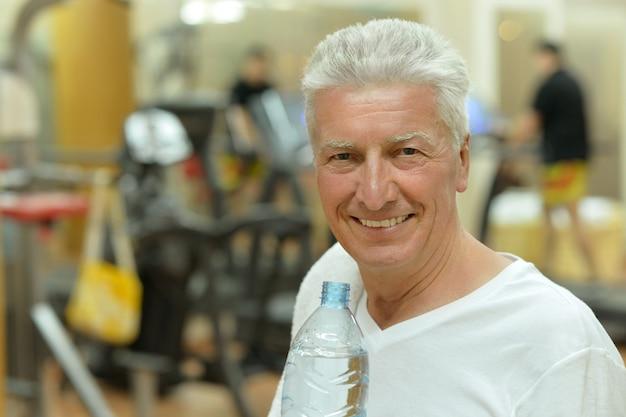 Älterer mann in einem fitnessstudio. wasser trinken nach dem sport