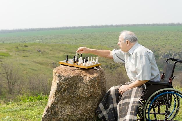 Älterer mann in einem rollstuhl, der draußen schach spielt