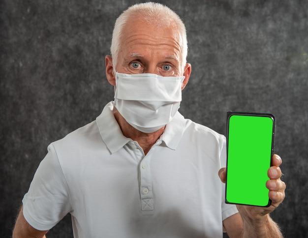 Älterer mann in einer medizinischen maske, die smartphone mit grünem bildschirm zeigt