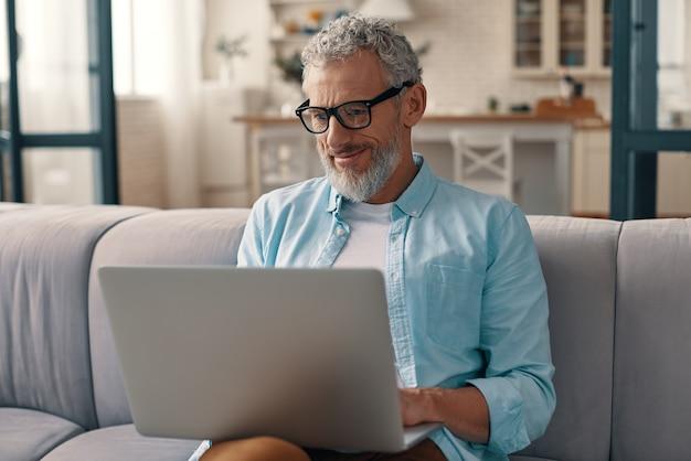Älterer mann in freizeitkleidung und brille mit laptop und lächelnd, während er zu hause auf dem sofa sitzt