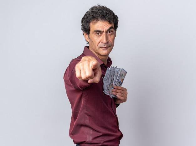 Älterer mann in lila hemd, der bargeld hält und mit dem zeigefinger auf die kamera zeigt, die mit ernstem gesicht über weiß steht