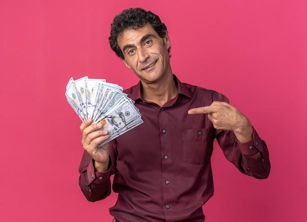 Älterer mann in lila hemd, der bargeld hält und mit dem zeigefinger auf geld zeigt, fröhlich lächelnd in die kamera schaut, die über pink steht