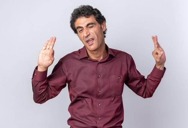 Älterer mann in lila hemd, der die kamera anschaut, ist glücklich und fröhlich und tut ein gutes zeichen, das auf weißem hintergrund steht