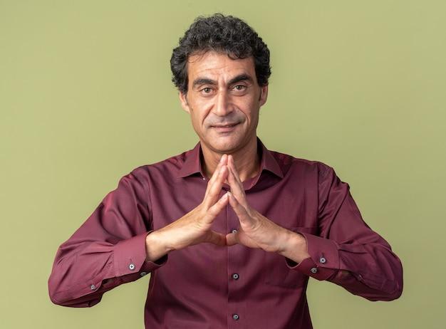 Älterer mann in lila hemd, der die kamera mit selbstbewusstem lächeln im gesicht anschaut und die handflächen zusammenhält und auf etwas wartet, das über grün steht