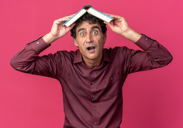 Älterer mann in lila hemd, der ein offenes buch über dem kopf hält und überrascht und erstaunt aussieht, als er über rosafarbenem hintergrund steht