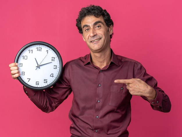 Älterer mann in lila hemd, der eine wanduhr hält, die mit dem zeigefinger darauf zeigt, glücklich und positiv lächelnd auf rosafarbenem hintergrund stehend
