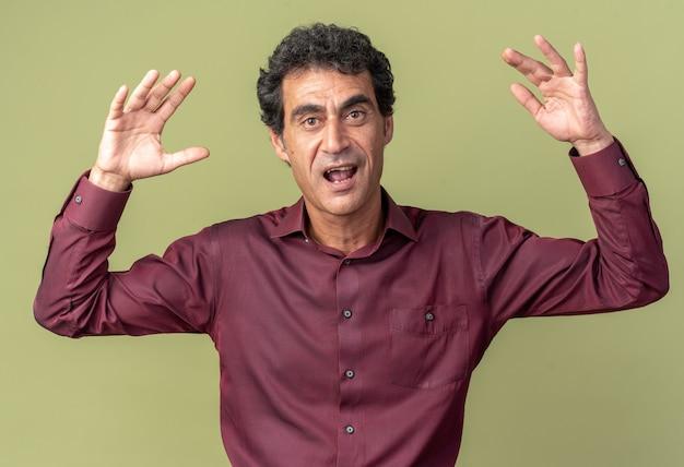 Älterer mann in lila hemd, der glücklich und aufgeregt in die kamera schaut, mit erhobenen armen über grünem hintergrund stehend