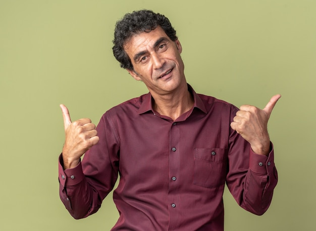 Älterer mann in lila hemd, der glücklich und positiv in die kamera schaut und daumen nach oben über grün zeigt