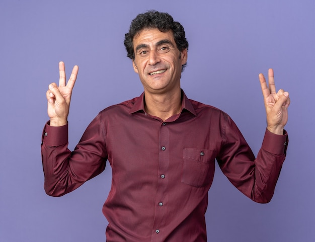 Älterer mann in lila hemd, der glücklich und positiv in die kamera schaut und ein v-zeichen über blau zeigt