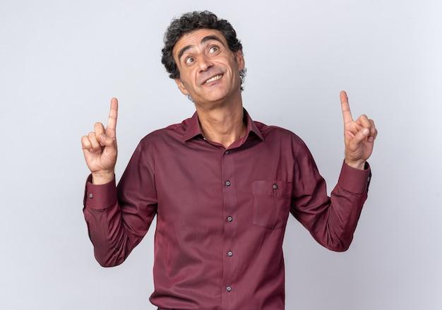 Älterer mann in lila hemd, der glücklich und überrascht aufschaut und mit den zeigefingern nach oben auf weißem hintergrund zeigt