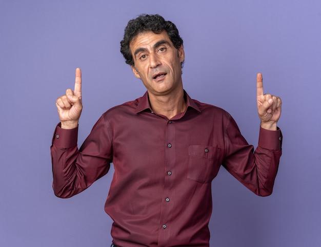 Älterer mann in lila hemd, der mit ernstem, selbstbewusstem ausdruck in die kamera schaut
